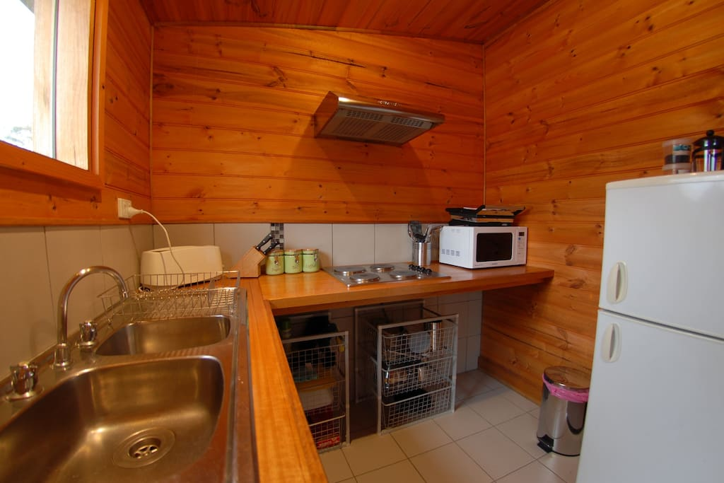 Small self contained kitchen with dishwasher, electric cooktop, microwave, fridge & coffee pod machine