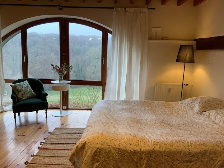 Chambre douce avec vue sur le bois et la campagne.