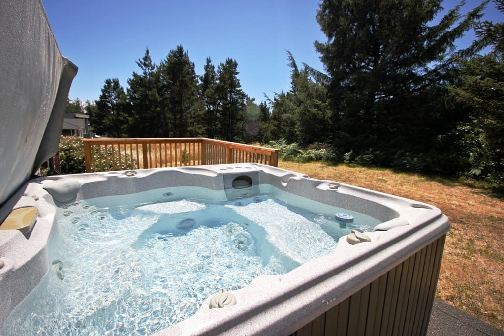 Back view of Sea Escape with a grassy backyard, back deck with hot tub and stone patio with picnic table.
