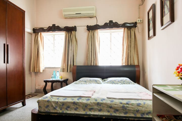 This is the bedroom with a king size double bed . There are 2 windows and a big almirah to store your belongings. There is free wifi with high speed as well as a Tv . The room has good lighting fan and Ac .It has  an attached washroom.