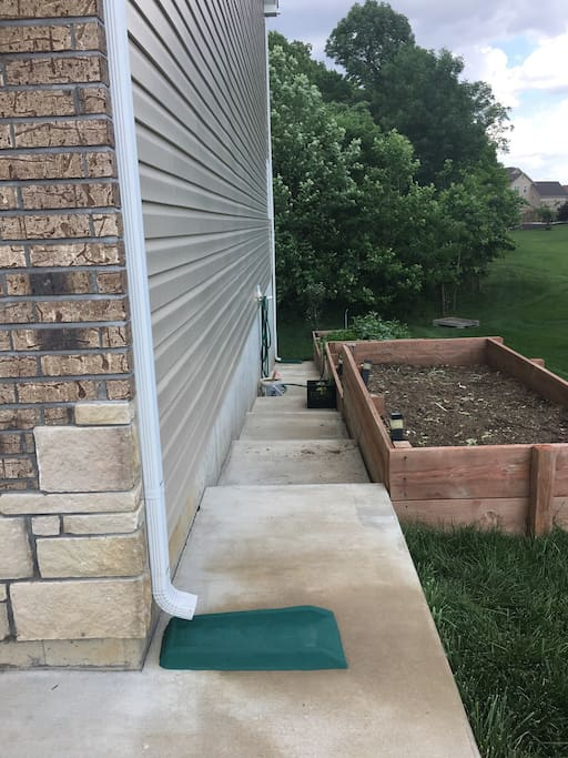 Slopping garden and stairs leading to apartment entrance.