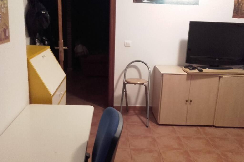 Cuarto con armarios y muebles y televisor plano.