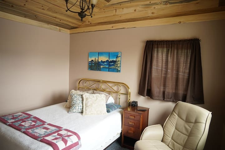 This is the main bedroom, with a queen size bed, a big window to view the mountains, a TV, recliner and A/C.