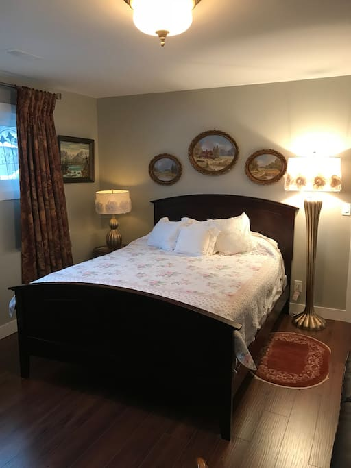 Bedroom G with a queen bed located in the basement with a wood burning fireplace