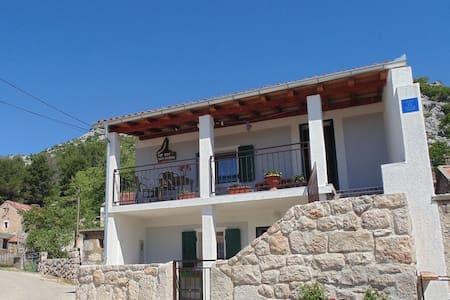 Traditionele vrijstaand stenen huis naast het Nationaal park. Overdekt terras