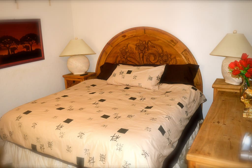The bedroom with a custom headboard, nightstands and dresser. Hand made here locally in San José. A comfortable bedroom with air conditioning.