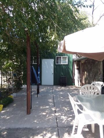 Back patio area, a lot of shade with hammock and BBQ Grill.