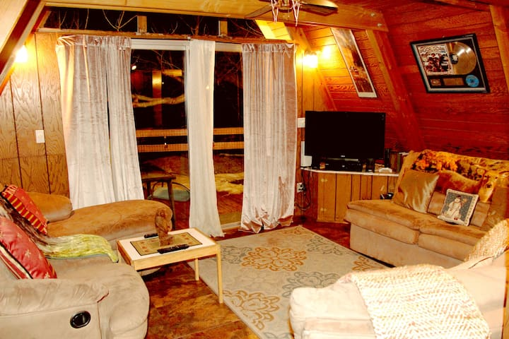 """Living Room. Plush Reclining seats, Sofa Bed, 40"""" Flat Screen, great Surround Sound for movies or for music! Sliding door opens to Rap Around Deck. New Claystone floors to match the majestic natural boulders that the cabin sits on, and all around!"""