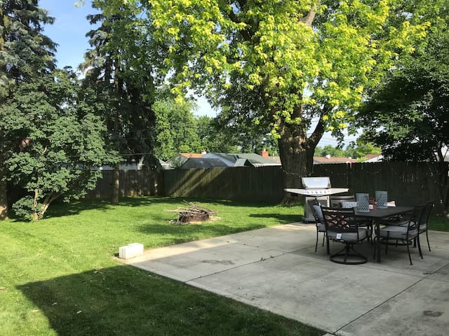 Fenced in back yard with patio, grill, fire pit.