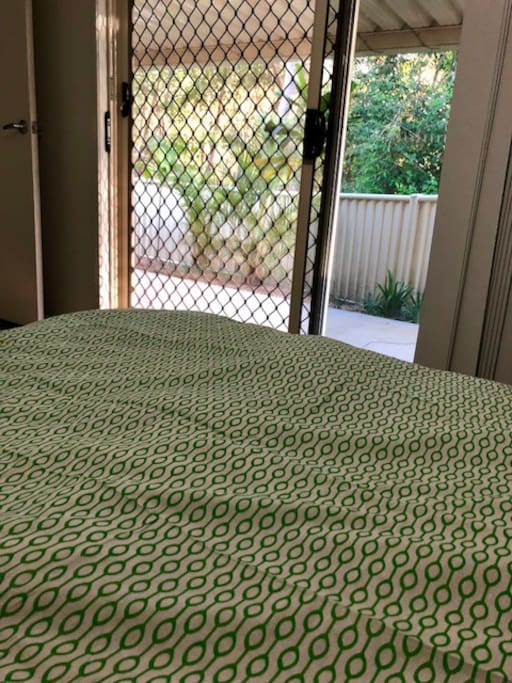 The bedroom has a very green and peaceful outlook