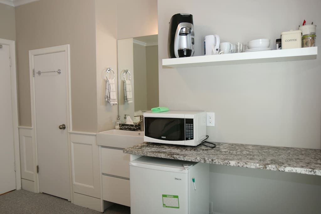 Sink, Kitchenette with microwave, coffee maker, kettle, small fridge