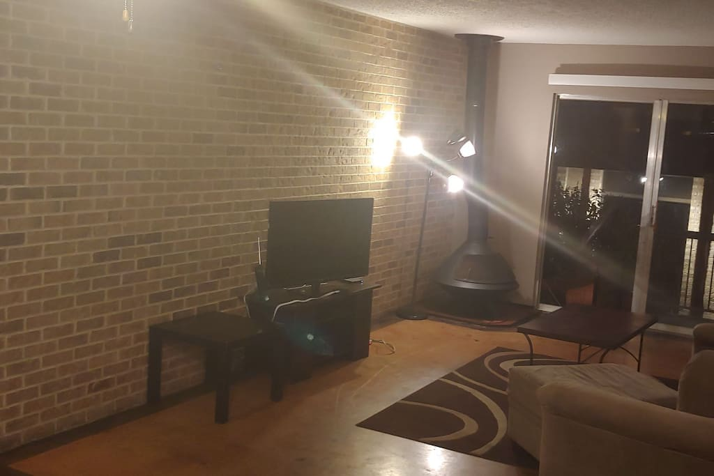 Spacious living area with brick wall and fire place