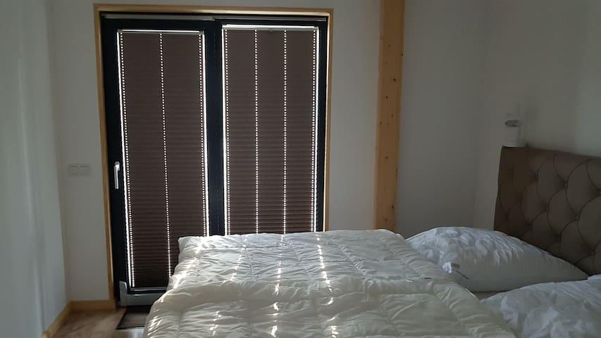 Schlafzimmer mit Verdunklungs-Plisses und Boxspringbett