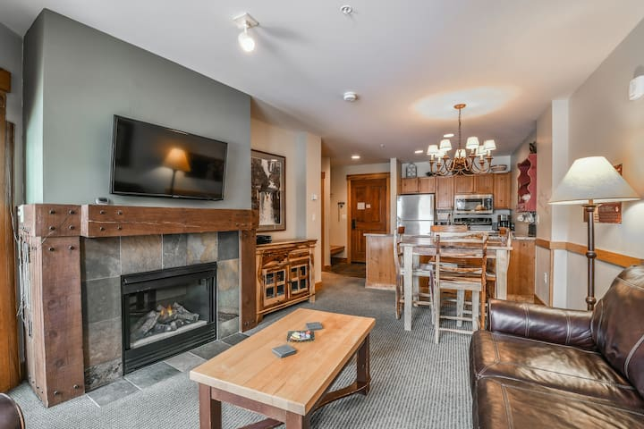 A big living room with a flat screen TV and a nice fireplace to warm up on a cool day