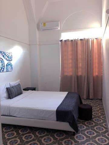 Vista al área de habitación la cual cuenta con una cama Queen size, mesita de noche, y todas sus almohadas y sabanas.