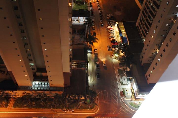 Vista da Avenida Araucárias pela janela do flat no início da noite.