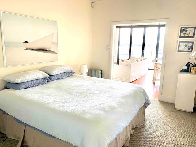 Our King bedroom is adjacent to the open plan living area, it is a new bed with new carpet and plenty of space for a cot.