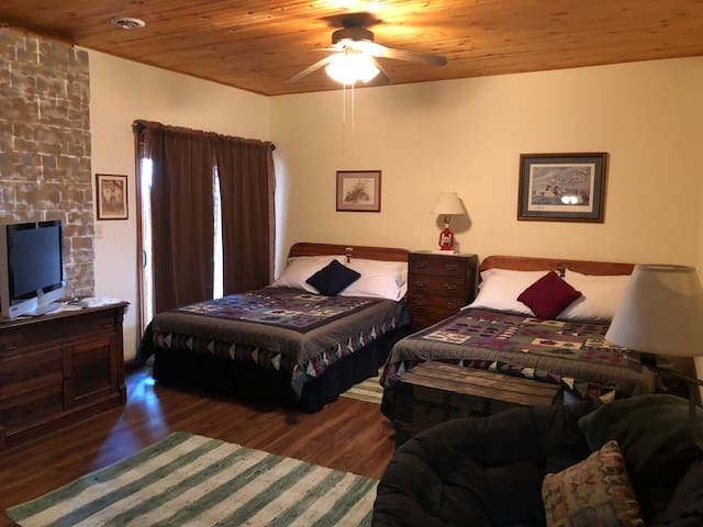 The lodge bedroom has two queen beds, a private bathroom, flat screen tv (with DirecTV) and a sliding glass door.