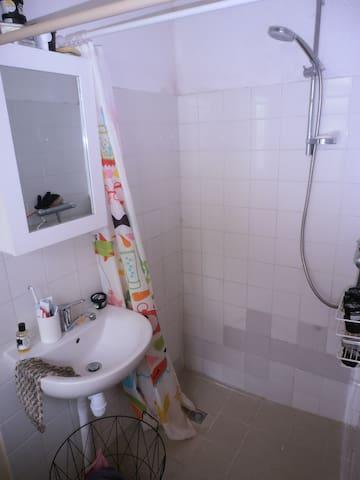 Salle de bain avec vasque et miroir.
