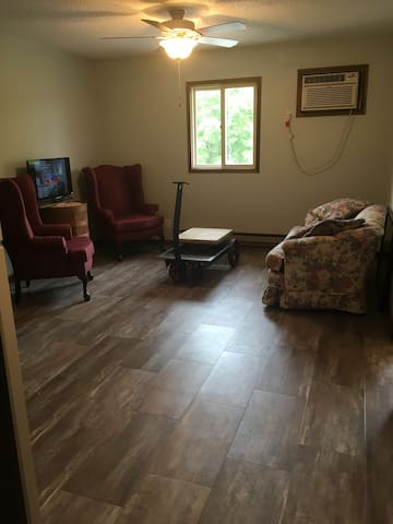 Living room area with tv, 2 arm chairs and love seat.
