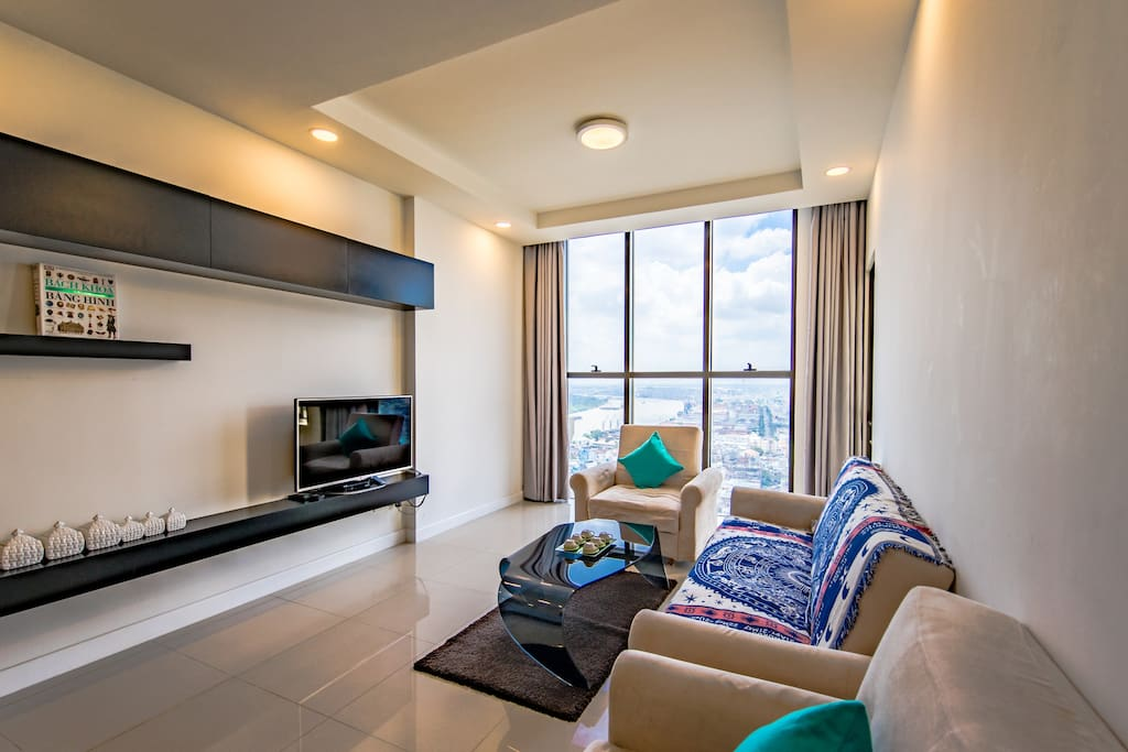 Living room with full-wall window, letting lights in and offering you a breath-taking view