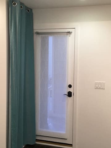 The front door from inside. The blue curtain swings over for privacy.