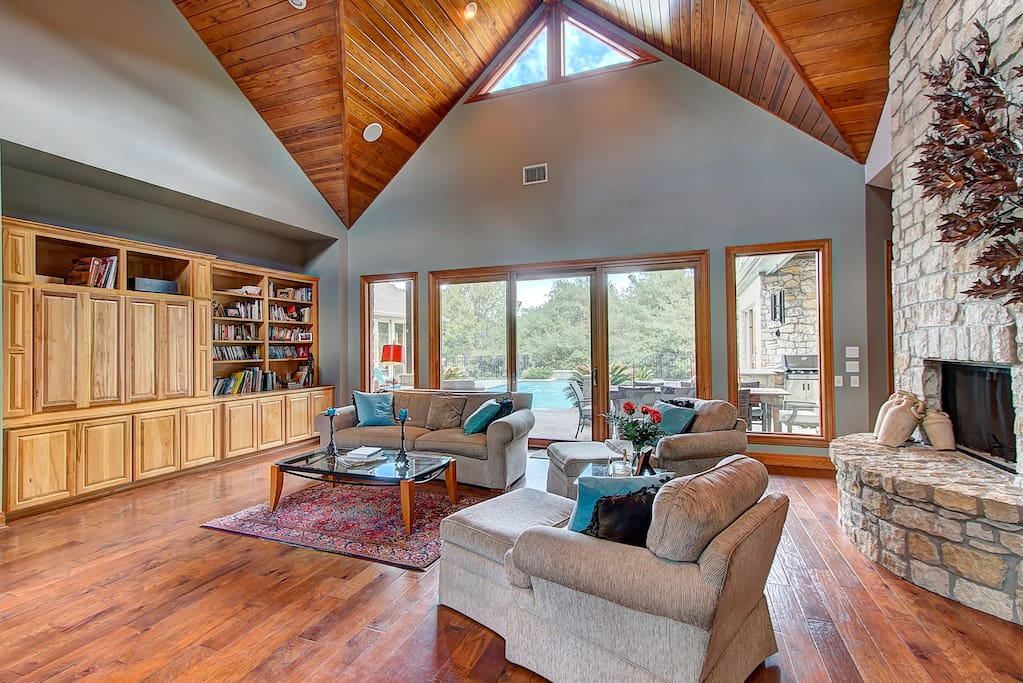 The artisan cathedral ceiling in this spacious living room is impressive yet warm and inviting with open views of the crystal pool and Hillcountry acerage beyond.