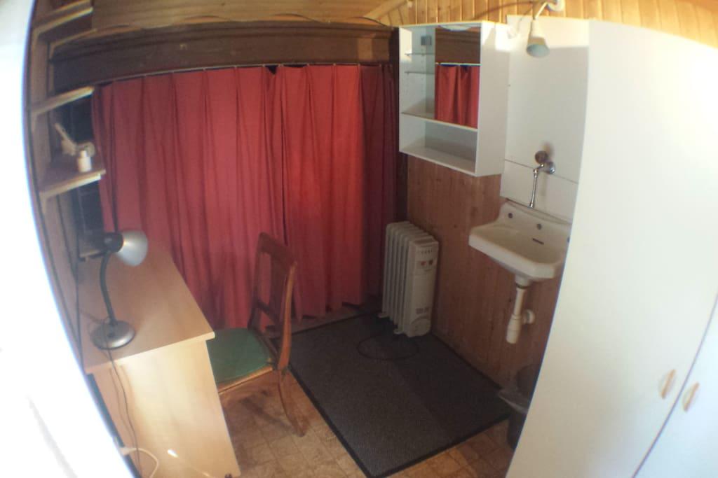 Lavabo d'eau froire et petit bureau de travail.
