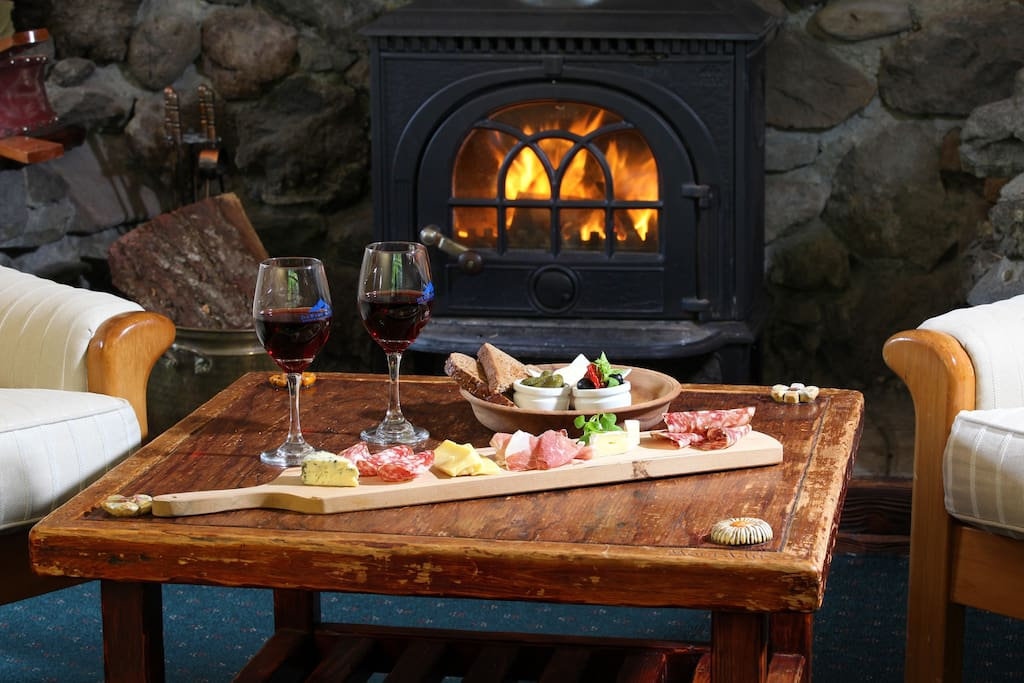 Enjoy a glass of wine alongside the fireplace in our guest lounge