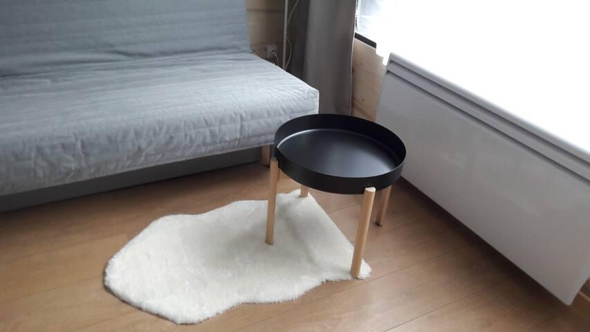 Espace salon avec canapé clic clac et petite table/desserte