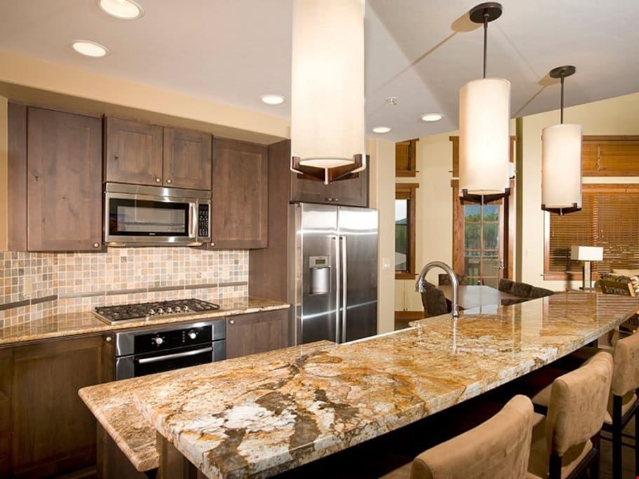 The fully-equipped kitchen features granite countertops, stainless steel appliances and a breakfast bar
