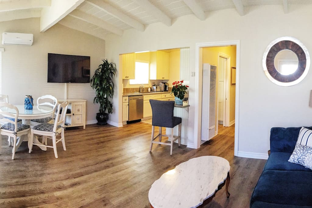 """Panoramic of open living, dining and kitchen area.  55"""" Samsung TV with all the goodies!"""