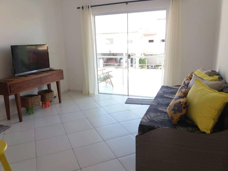 Sala arejada com televisão e sofá bicama