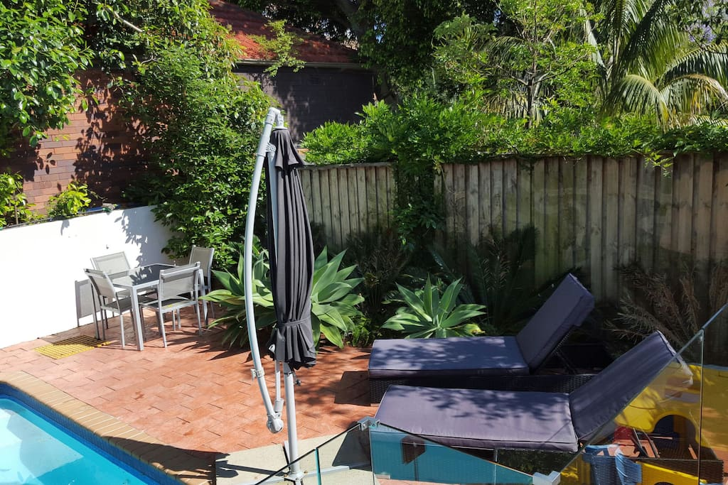 Deck area beside swimming pool with two padded sun lounges, shade umbrella and 4 seat table.