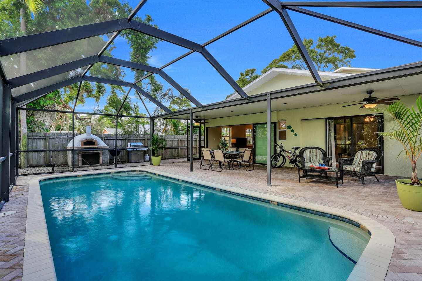 Screened pool, covered lanai and dining area, brick pizza oven, charcoal grill and gas grill