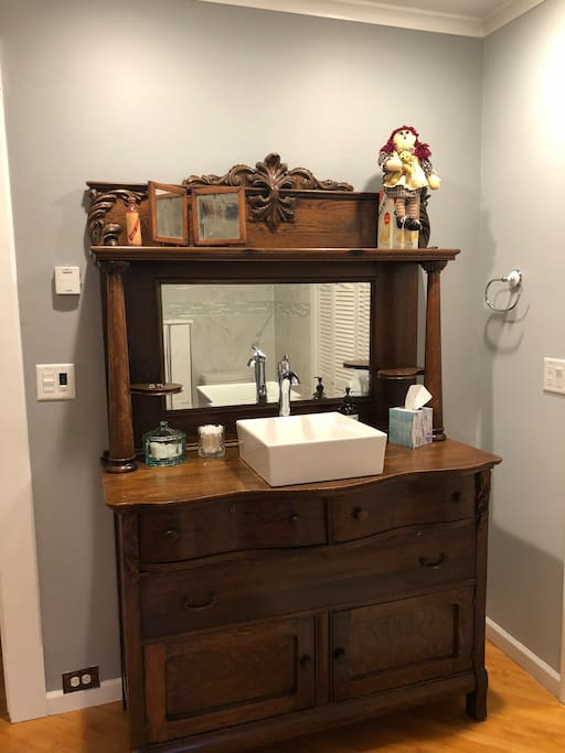 Antique vanity converted into sink to keep with the time period of the home.