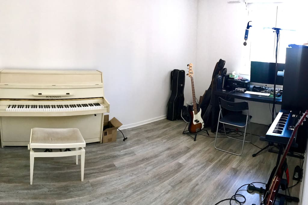 Music room equipped with a piano, an electric guitar, a bass, a synth and a mic. The iMac is available for recording on Logic X with NI Komplete.