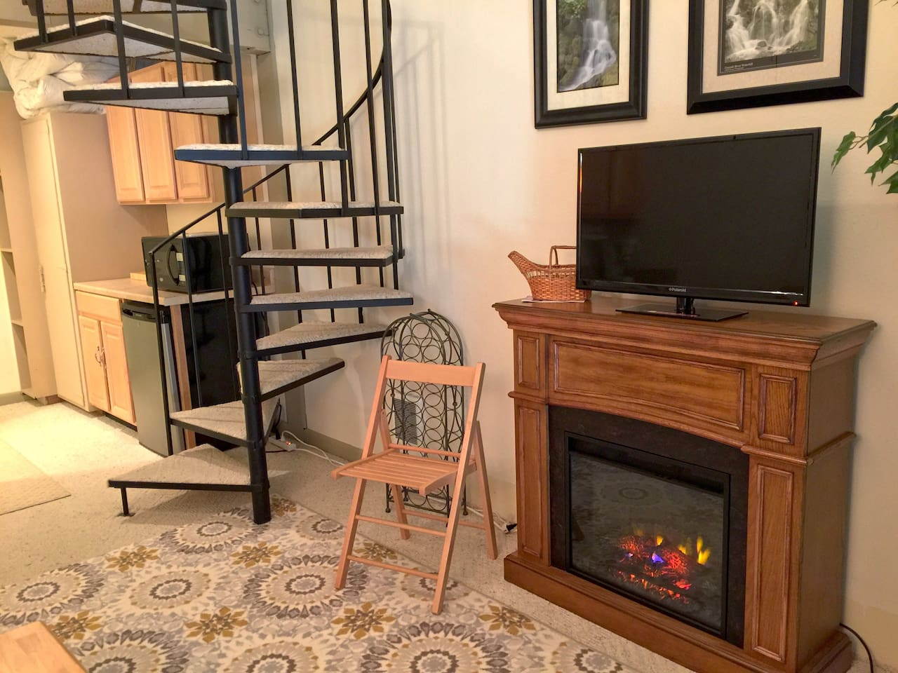 Cozy living room, electric fireplace, Cable TV, Wifi, dishwasher, microwave and staircase to the bedroom.