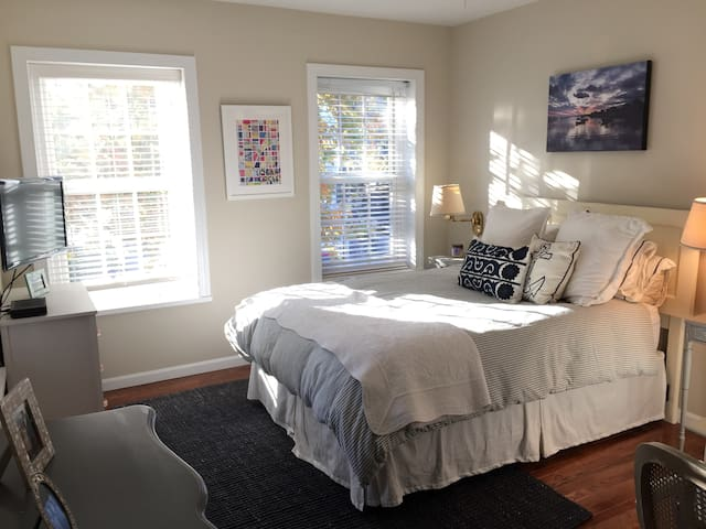 Light-filled master bedroom with a queen-sized bed and cable TV