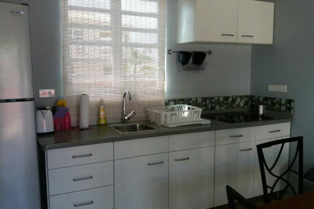 Spacious kitchen with utensils, cooking plate and refrigerator.