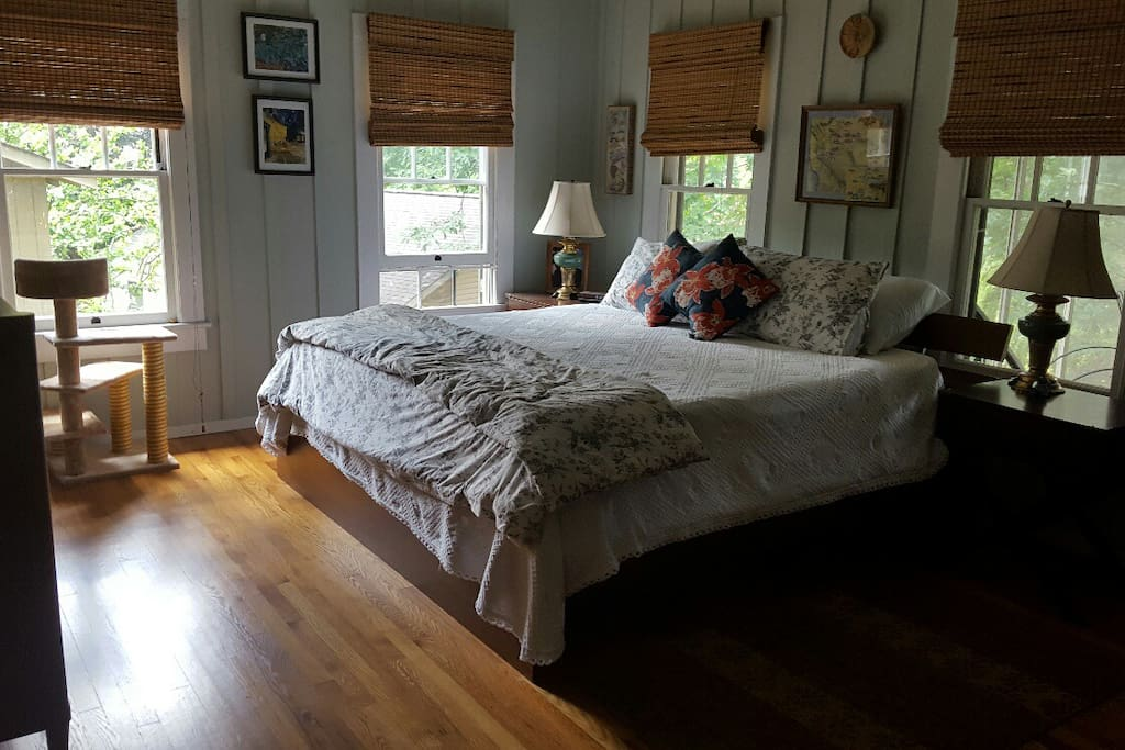 large bright bedroom with hardwood floors connects to porch and kitchen area