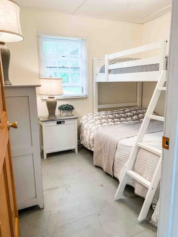 The bunk room is a full sized mattress on the bottom and twin on top. We offer a side table with 2 USB ports and an extra electric plugin next to the bed. The top bunk would require an extra long cord or short extension cord to reach the top bunk.