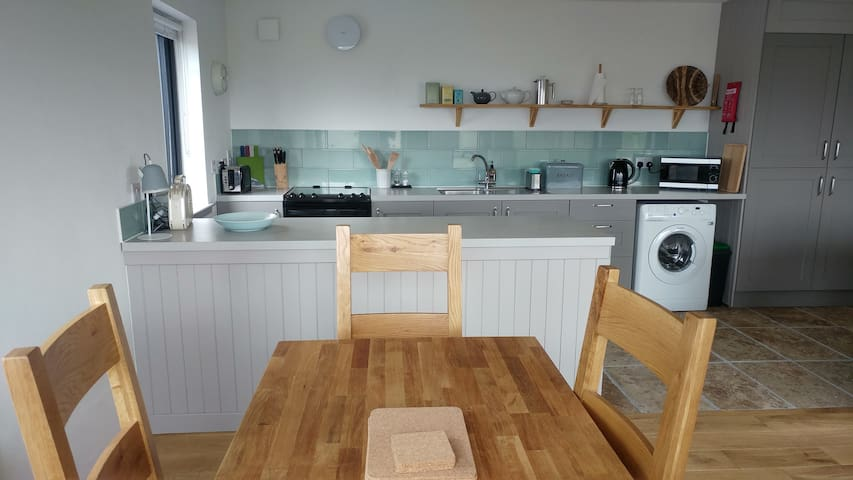 Kitchen area with a full size cooker, fridge, toaster, cafetière and a microwave.