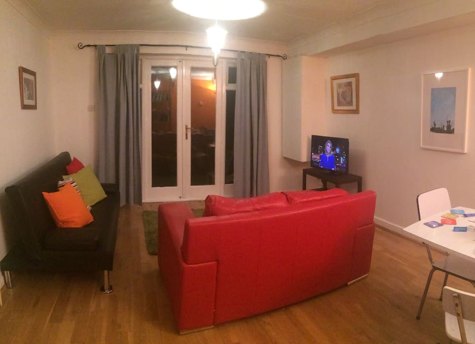 This is the living room. There is a double sofa bed and French windows leading to the garden.