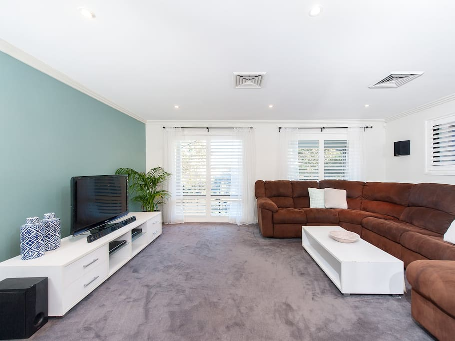 Main lounge room. Sofa seats 8. Foxtel. Blu ray and sound bar with blue tooth. Beautiful view of sunset. Two doors can section off this room to keep the noise in.