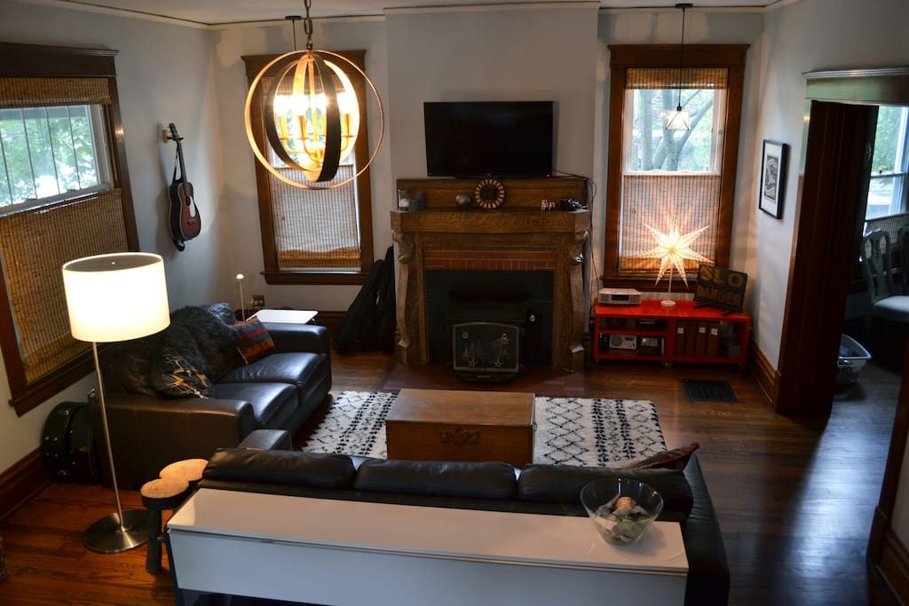 Large, open living room with leather couches, Morrocan shag rug, flat-screen TV, art/antiques, and good lighting