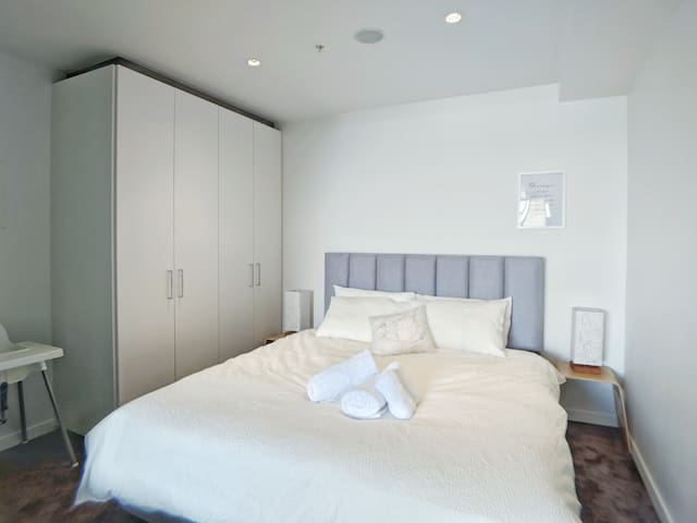 Bedroom 2. Also a king bed. Wardrobe with hangers. Although no window, with big frosted glass sliding doors and blinds.