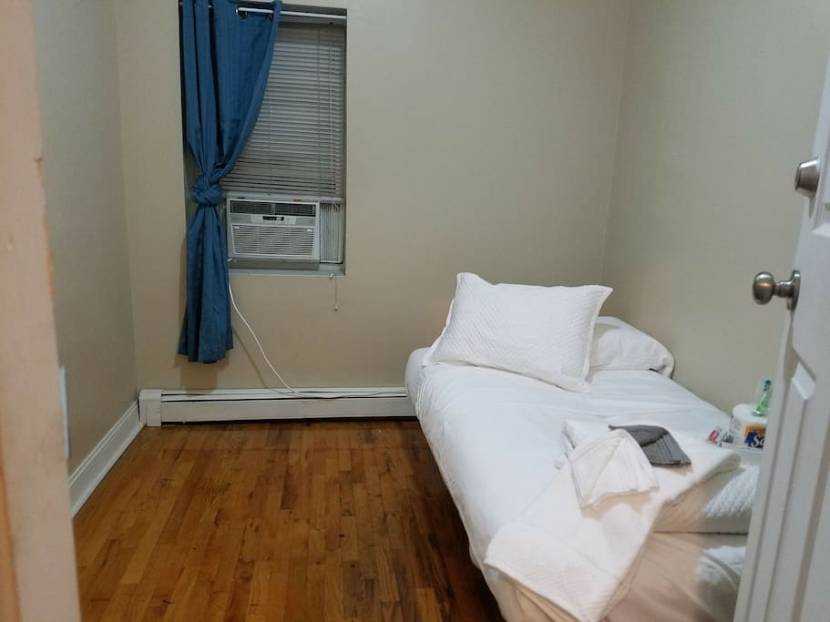 Full size comfortable bed with hard wood flooring