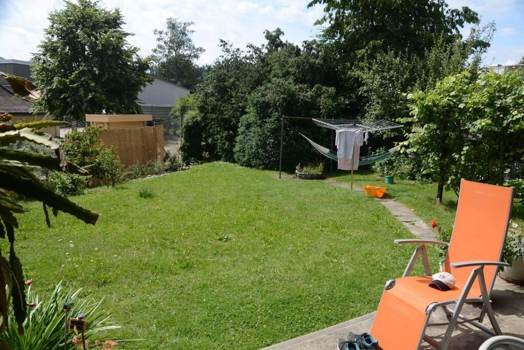 sonniger Garten, mit Blumen und Bäumen: zum Geniessen ist und Badmintonspiel oder im Zelt zu übernachten(Kinder)