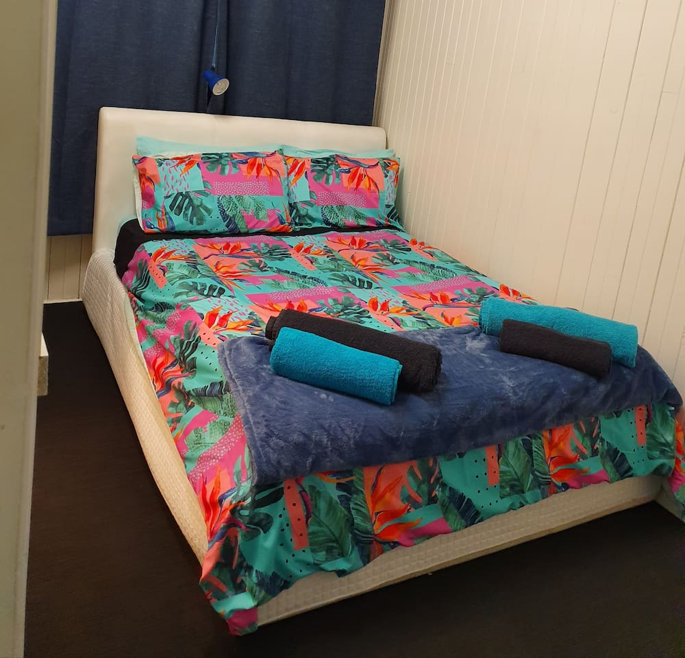 Double bed in bedroom with storage under, 2 pillows per guest bed has top and bottom sheets we have put different coloured sheets to make it obvious, bath towel, bath sheet and a face cloth are provided for each guest, also block out curtains